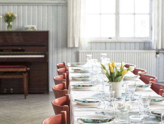 Kuvassa Rauhanaseman juhlasaliin on katettu pitkä pöytä. Pöydällä on valkoinen pöytäliina, tulppaaneja ja astiat. Taustalla näkyy ikkuna ja piano, jonka päällä on keltaisia kukkia.