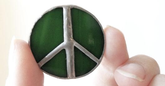 Vihreä rauhanmerkkikoru sormien välissä.