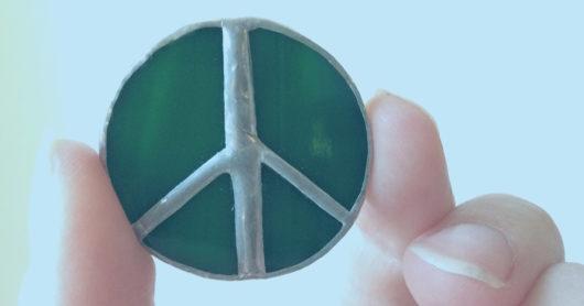 Sormet pitelevät vihreäsävyistä rauhanmerkkikorua vaaleaa taustaa vasten