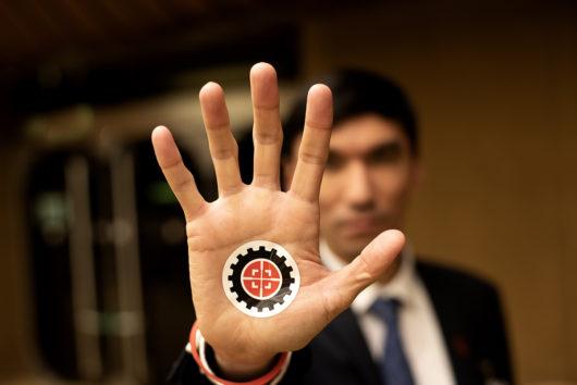 Tappajarobotteja vastustavan kampanjan aktiivi on kohottanut käden kohti kameraa. Kämmenessä kampanjan logo.