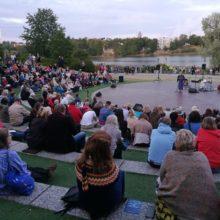 Töölönlahden amfiteatteri, ihmisiä istuu kuuntelemassa puhetta.