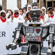 Robottiaseiden vastaisen kampanjan tempaus, etualalla robotti ja takana valkoisiin haalareihin pukeutuneita ihmisiä