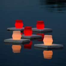 Atomipommien uhrien muistoksi mereen laskettuja punaisia ja valkoisia kynttilälyhtyjä hämärtyvässä illassa