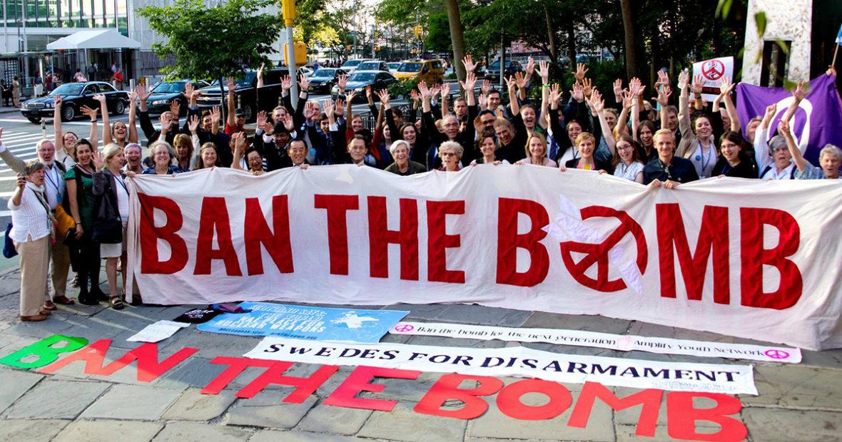 """Joukko ydinasekieltoa kannattavia aktivisteja hurraa ja pitelee valkoista banderollia, jossa lukee punaisin kirjaimin """"Ban the Bomb""""."""