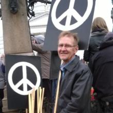 Mies mielenosoituksessa. Pitelee kylttiä, jossa on rauhanmerkki.