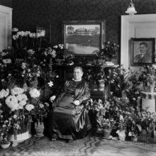 Lucina Hagman istuu tuolissa huoneessa, ympärillä on kukkia.