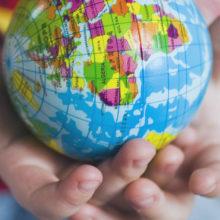 Lapsen kädet pitelevät maapallokuvioitua palloa