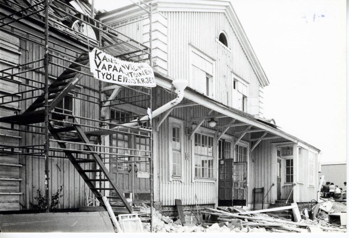 Rauhanasema kesken kunnostuksen. Rakennustelineestä roikkuu banderolli, jossa lukee: Kansainvälinen vapaaehtoinen työleirijärjestö.