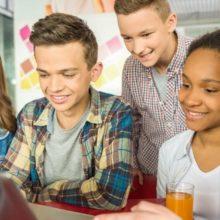 Viisi nuorta ja iloista opiskelijaa katsovat tietokoneen näyttöä.