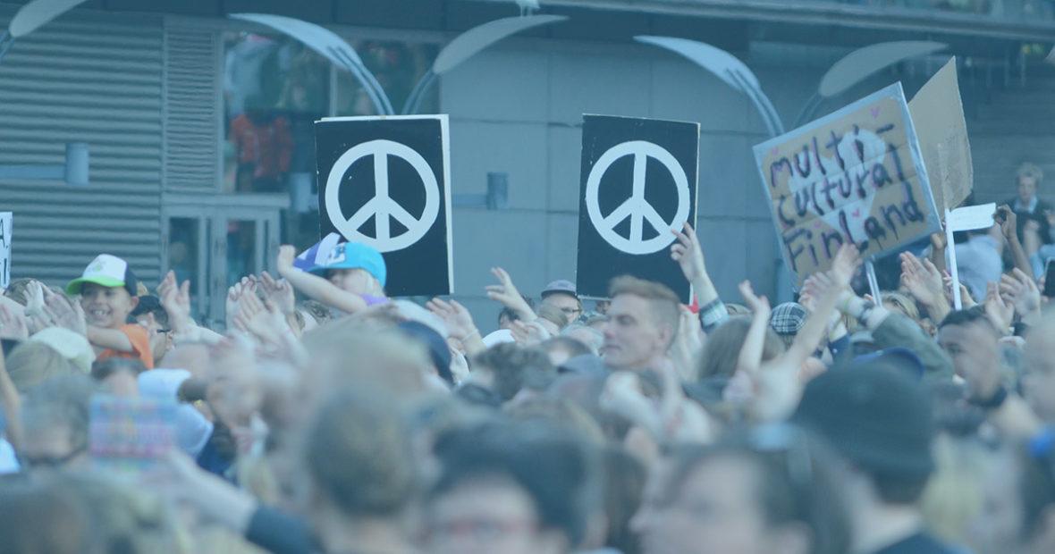 Kuva mielenosoituksesta, jossa takana ihmisten päiden yläpuolella nousee kaksi mustapohjaista, suurta mielenosoituskylttiä. Kylteissä on maalattu rauhanmerkit valkoisella.