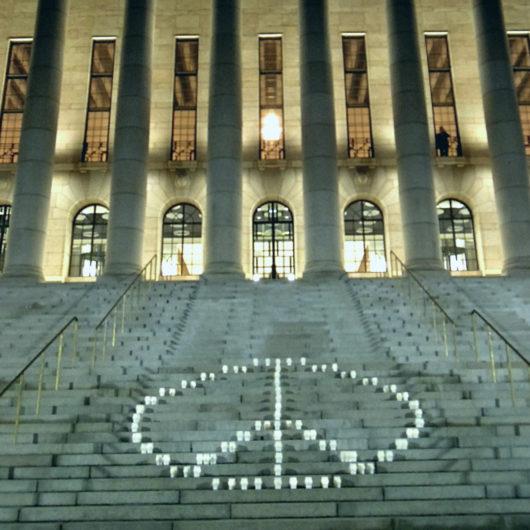 Kuvassa valkoisista kynttilälyhdyistä tehty rauhanmerkki eduskuntatalon portailla