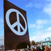 Mielenosoituskyltti, jossa on valkoinen rauhanmerkki mustalla pohjalla