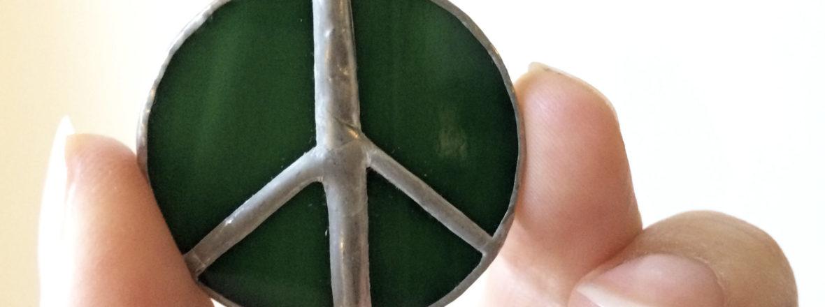 Lähikuva vihreästä rauhanmerkkikorusta, jota sormet pitelevät