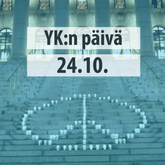 Teksti: YK:n päivä 24.10. Taustalla kuva rauhanmerkistä eduskuntatalon portailla